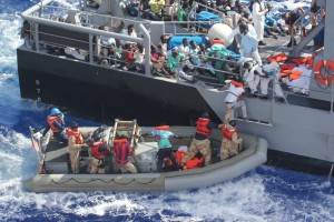 Flüchtlinge klettern nach ihrer Rettung von einem Schlauchboot des US-Marine-Schiffes USS San Antonio (LPD-17) auf ein Patrouillenboot der Republik Malta. By Official U.S. Navy Page from United States of America U.S. Navy photo/U.S. Navy [Public domain], via Wikimedia Commons